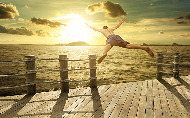 Jumping into the Ocean at Sunset, Summer Fun Lifestyle Jumping into the Ocean at Sunset, Summer Fun Lifestyle taking the plunge stock pictures, royalty-free photos & images