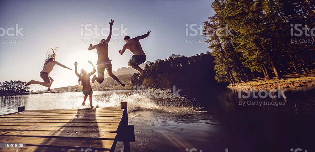 Salto en el agua desde el embarcadero - foto de stock
