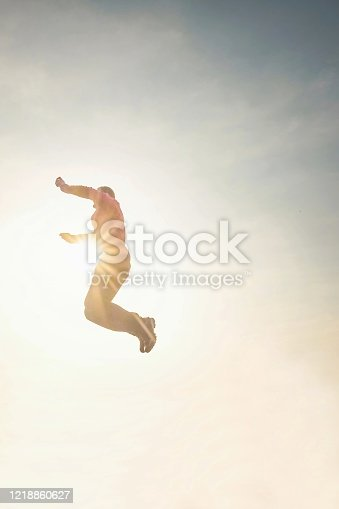 Jumping man in the sky.  Man jumping in the sunshine against blue sky. Concept: freedom, success, energy, vitality.