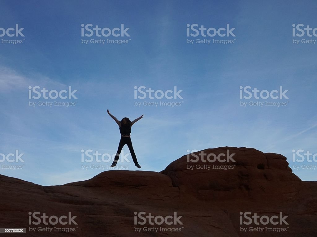 Jumping Mid-air Person Silhouette, Curved Rock Formation stock photo