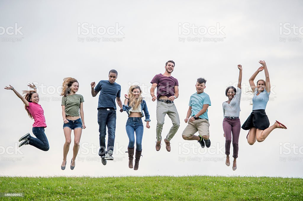 Jumping on a Grassy Hill Top stock photo