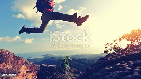 istock jumping over precipice between two rocky mountains at sunset 667470730