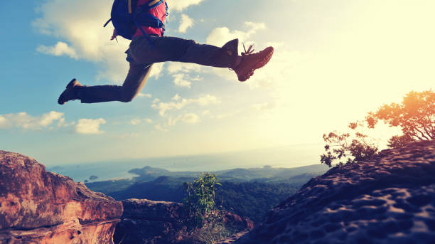 jumping over precipice between two rocky mountains at sunset stock photo