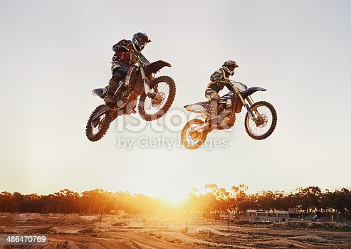 A shot of two motocross riders in midair during a race