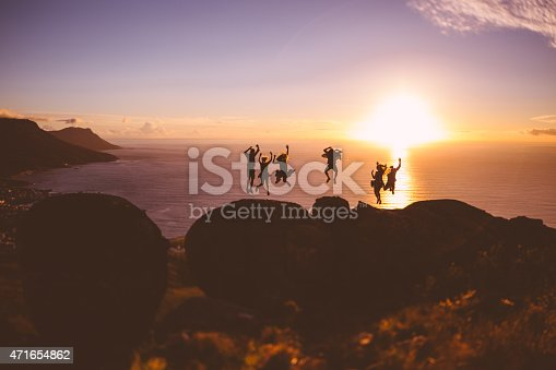 Joyful jumping silhouettes of people in front of the sun setting over the sea