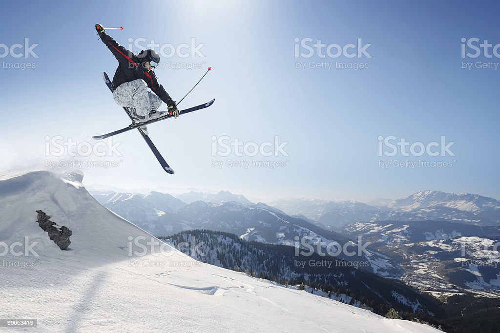 Jumping skier on a snowy mountain stock photo
