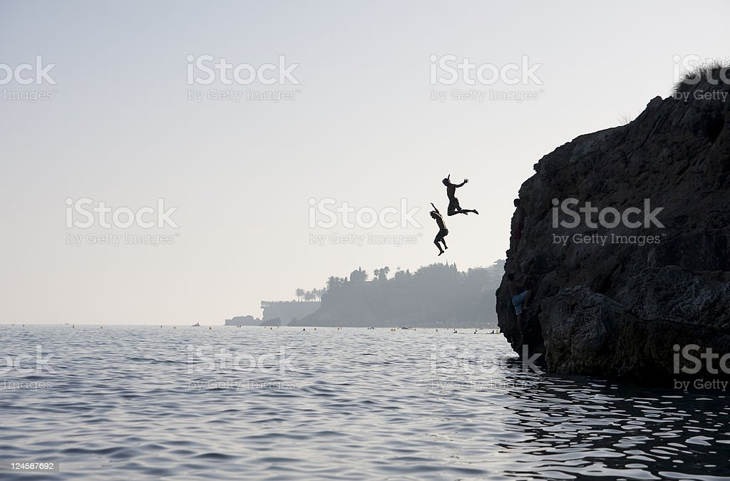 jumping to the water from cliff stock photo