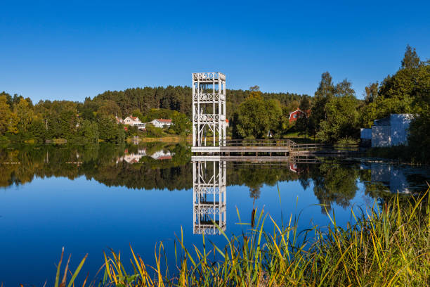 A jumping tower and traditional cottages stands by the lakeside in Hedemora, Sweden stock photo