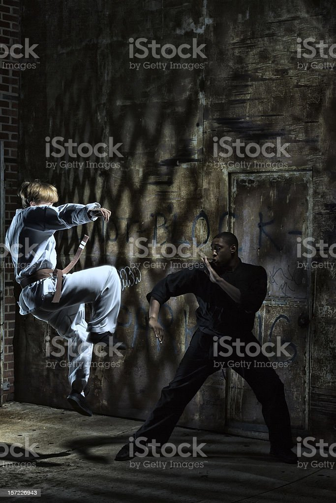 Jumping up to Kick in Kenpo Karate with Uniforms royalty-free stock photo