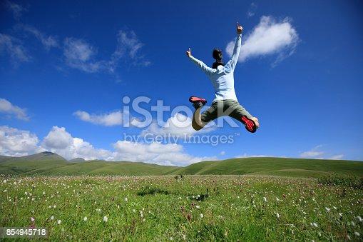 jumping woman have fun in a mountain peak meadow