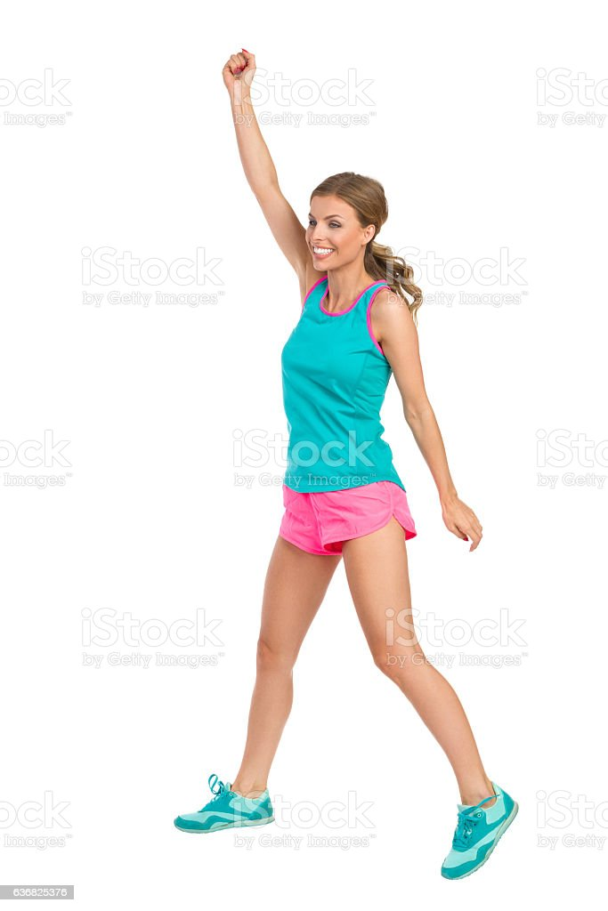 Jumping Woman In Sports Clothes Rising Arm stock photo