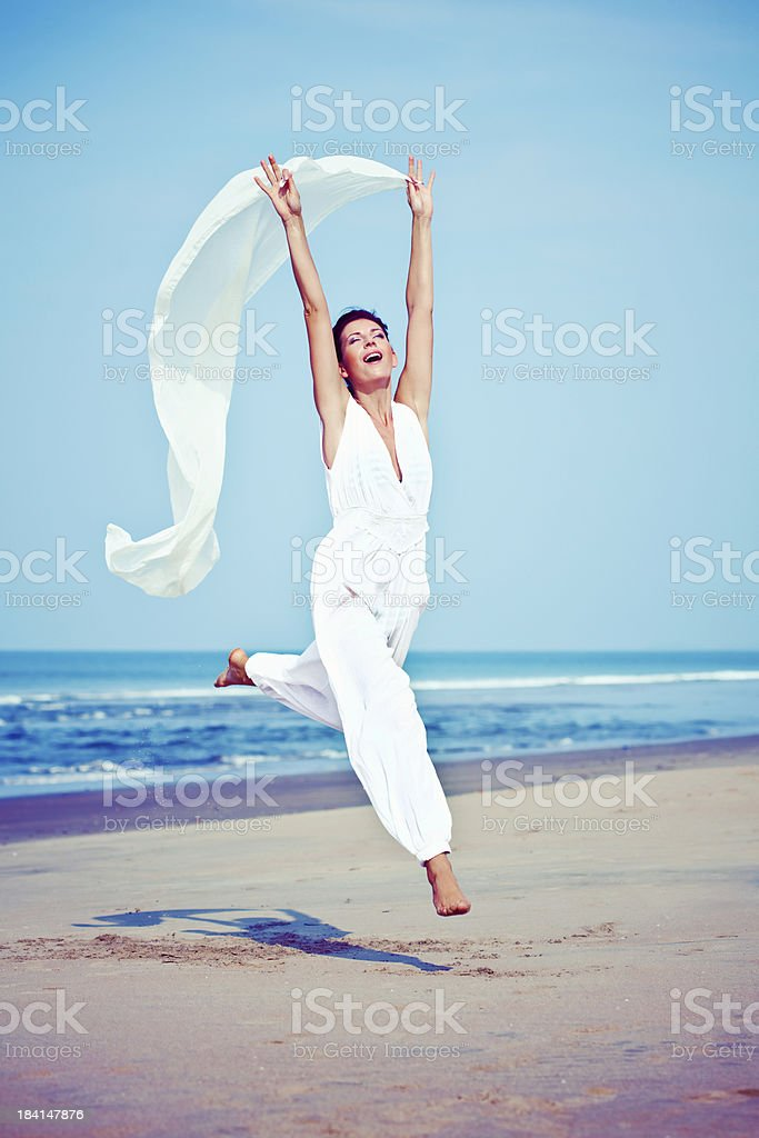 Jumping woman on the beach Happy woman jumping on the tropical beach, holding white shawl in her hands with wind blowing. 25-29 Years Stock Photo