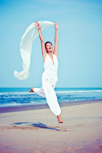 Jumping Woman On The Beach Stock Photo - Download Image Now