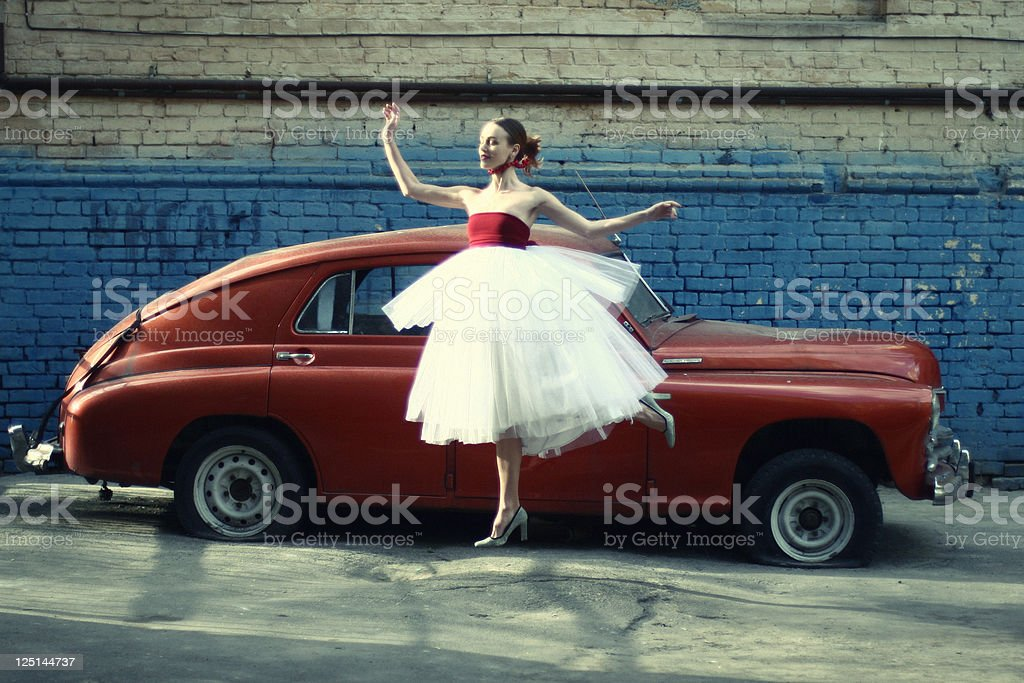 jumping women at retro car background stock photo
