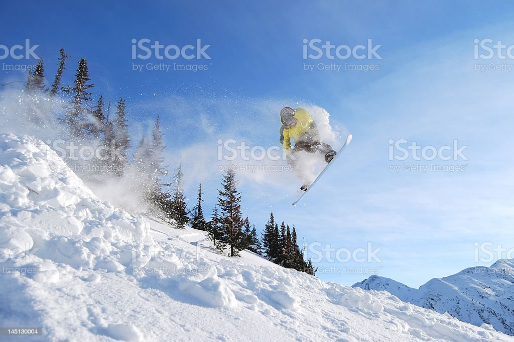 Jumping yellow snowboarder royalty-free stock photo