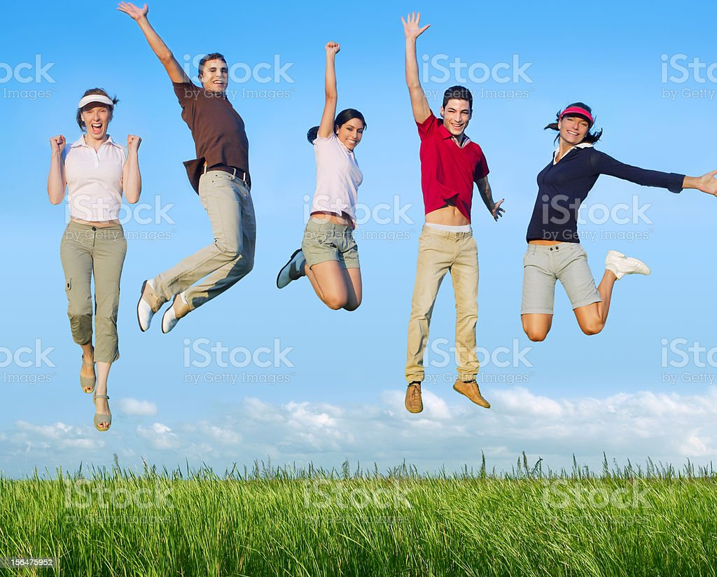 Jumping young people happy group in meadow stock photo