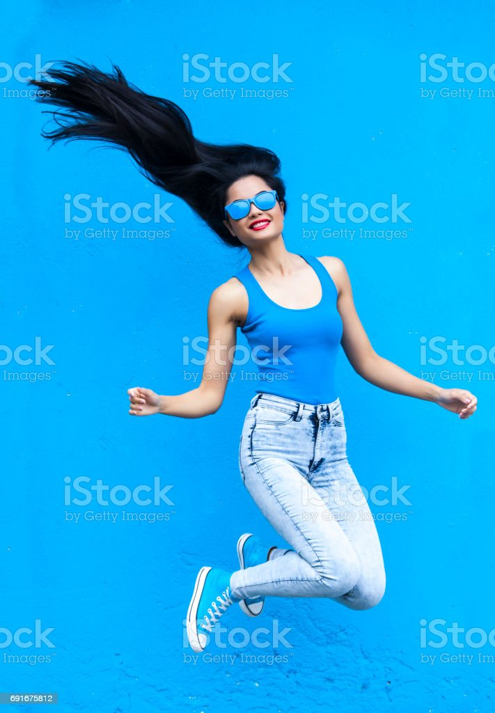 Jumping young woman stock photo