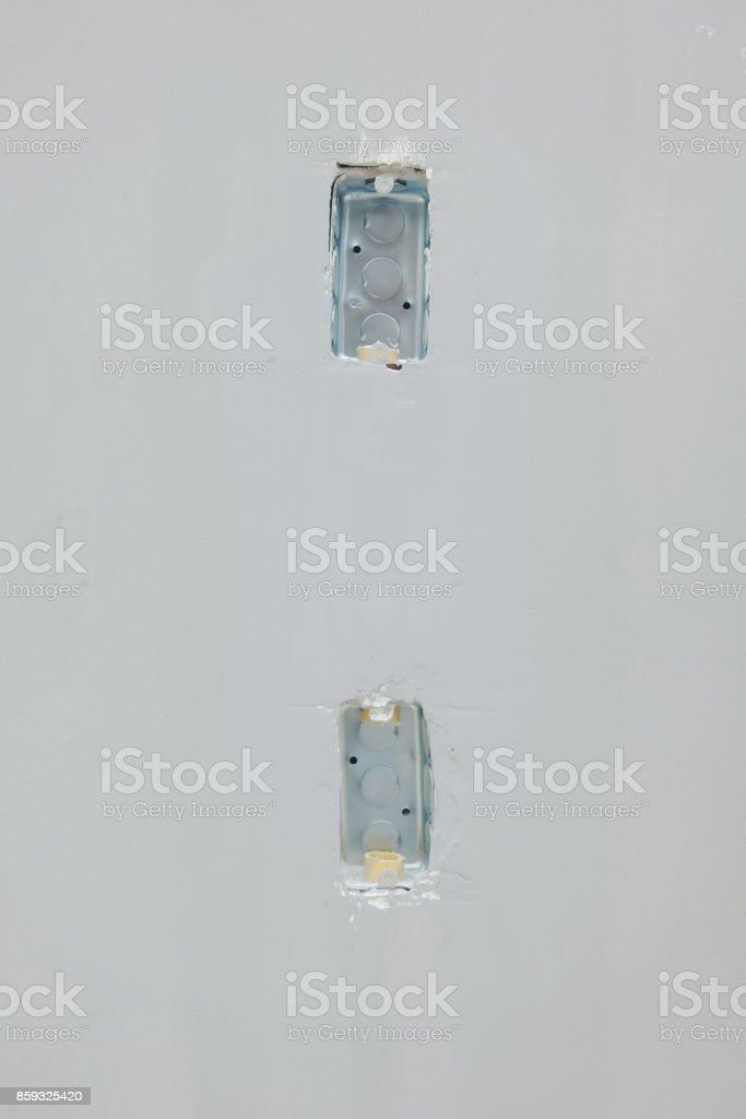 Junction boxes for switches on concrete wall at construction site stock photo