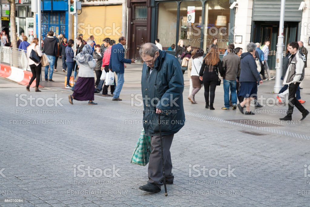 Junction in city centre. Elderly man crossing the road. stock photo