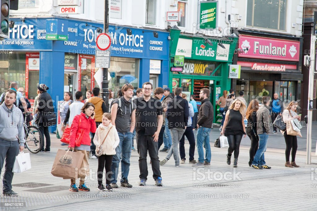 Junction in city centre. People look around for traffic. stock photo