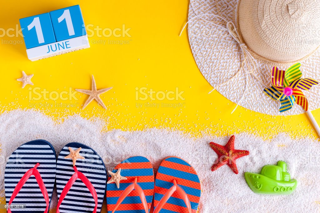 June 11th. Image of june 11 calendar on yellow sandy background with summer beach, traveler outfit and accessories. Summertime concept stock photo