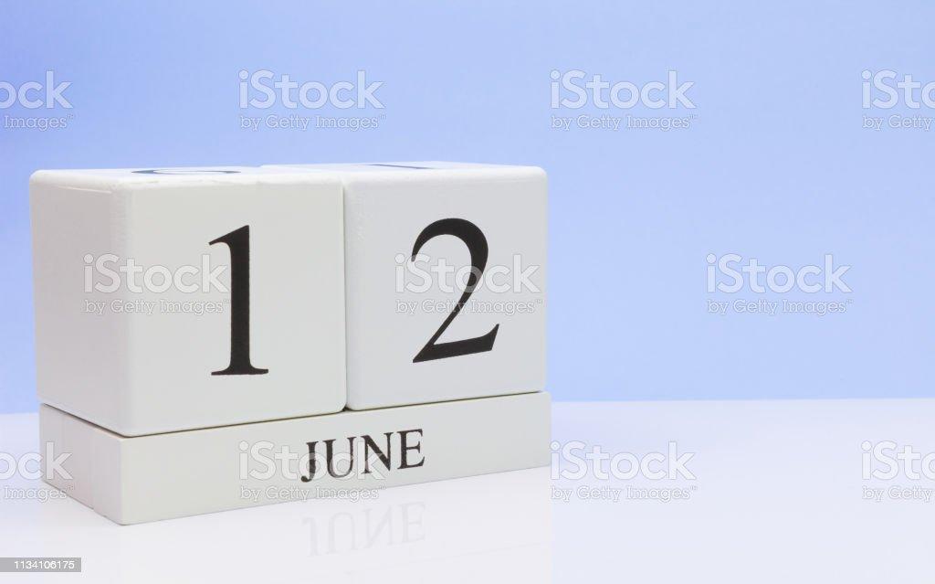 Junho 12ST. dia 12 do mês, calendário diário na tabela branca com reflexão, com luz-fundo azul. Tempo de verão, espaço vazio para o texto - foto de acervo