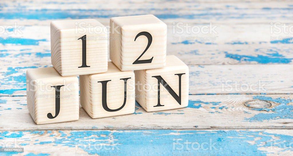 12 de junho. Cubos de madeira, com data de 12 de junho no antigo fundo de madeira azul. - foto de acervo