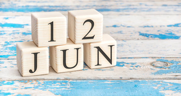 June 12th. Wooden cubes with date of 12 June on old blue wooden background. stock photo