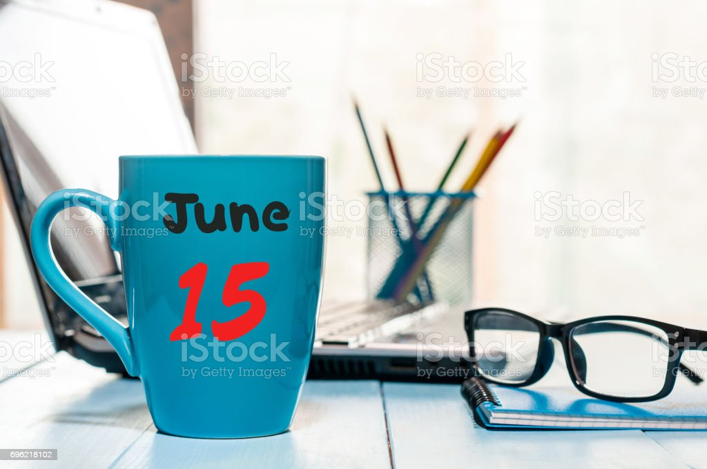 June 15th. Day 15 of month, color calendar on blue morning coffee cup at business workplace background. Summer concept. Empty space for text stock photo