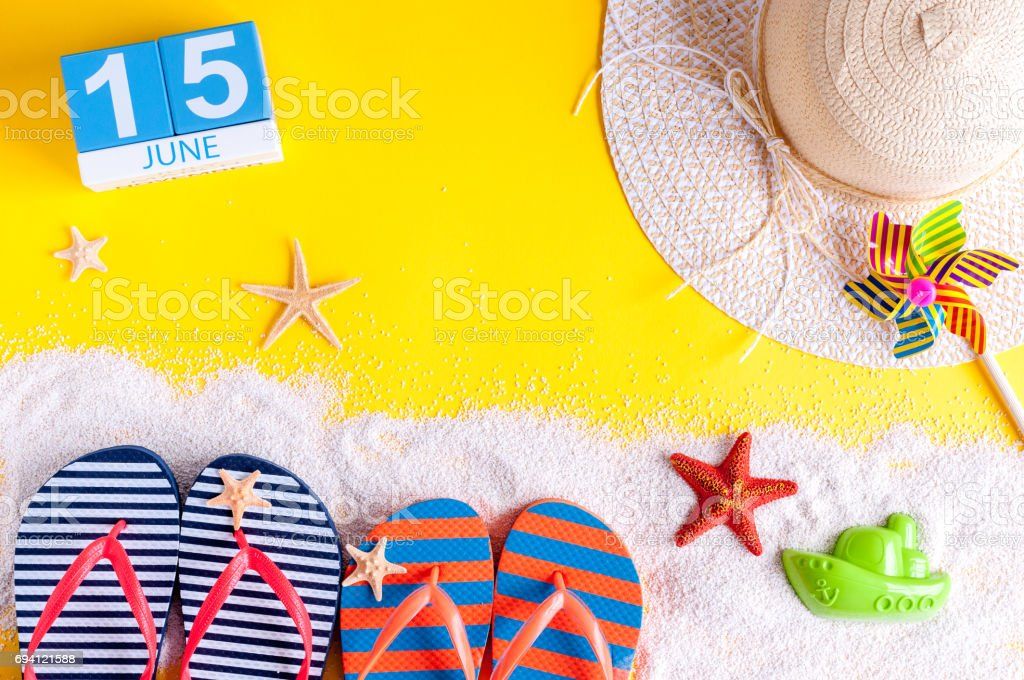 June 15th. Image of june 15 calendar on yellow sandy background with summer beach, traveler outfit and accessories. Summertime concept stock photo