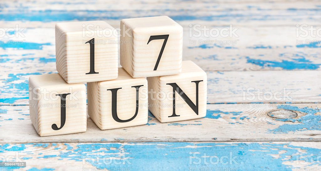 June 17th. Wooden cubes with date of 17 June on old blue wooden background. stock photo