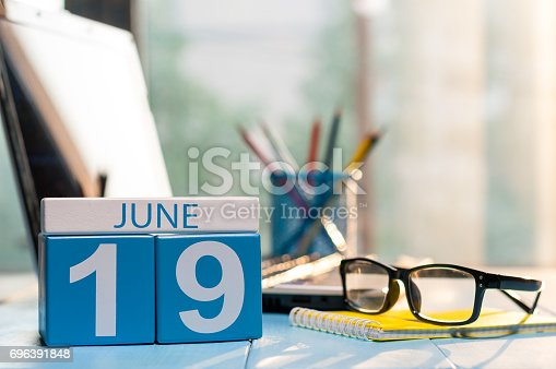 istock June 19th. Day 19 of month, wooden color calendar on audit office background. Summer time. Empty space for text 696391848