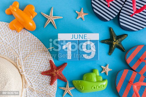 istock June 19th. Image of june 19 calendar on blue background with summer beach, traveler outfit and accessories. Summer day 691609794
