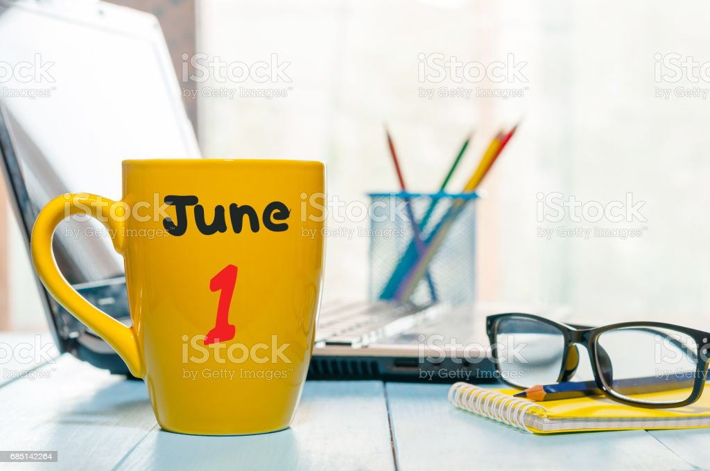 June 1st. Day of the month 1 , color calendar on morning coffee cup at business workplace background. Summer concept. Empty space for text stock photo
