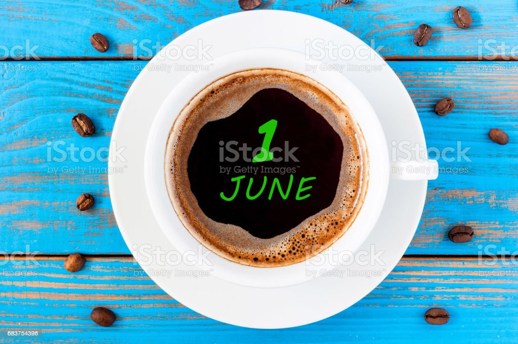 June 1st. Day of the month 1 , everyday calendar written on morning coffee cup at blue wooden background. Summer concept, Top view stock photo