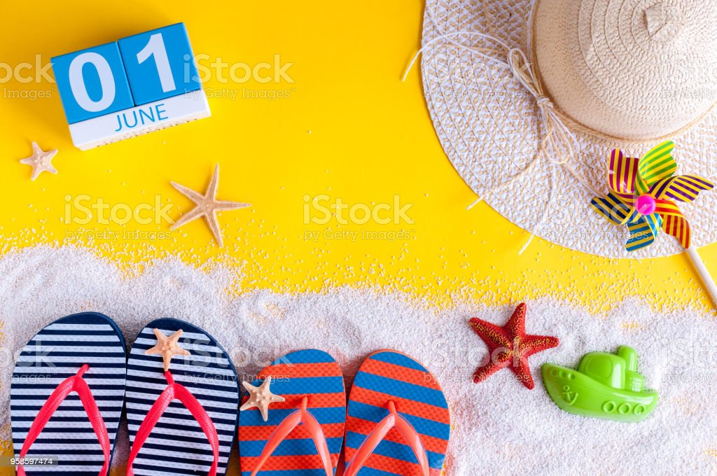 June 1st. Image of june 1 calendar on yellow sandy background with summer beach, traveler outfit and accessories. First summer day. Happy Childrens Day stock photo