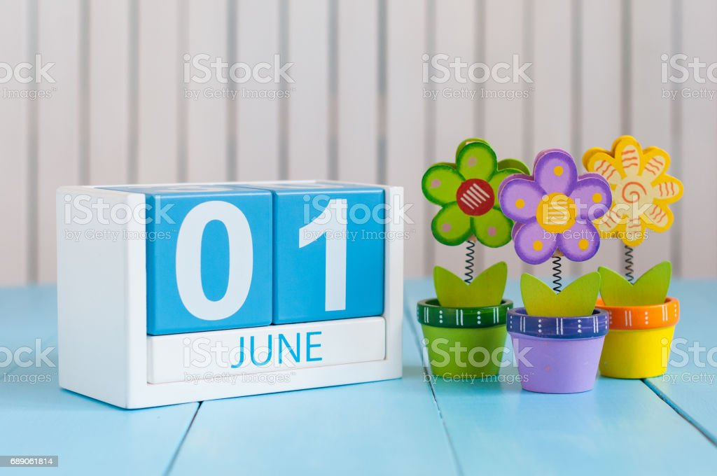June 1st. Image of june 1 wooden color calendar on blue background with flowers. First summer day. Empty space for text. Happy Childrens Day stock photo