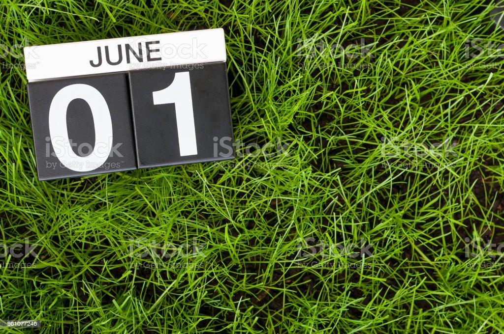 June 1st. Image of june 1 wooden color calendar on green lawn grass background. First summer day stock photo