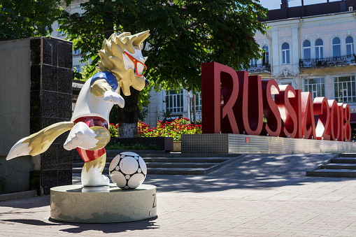 """ROSTOV-ON-DON, RUSSIA - 11 June, 2018 The official mascot of the 2018 FIFA World Cup and the FIFA Confederations Cup 2017 wolf Zabivaka  scores a goal. A monument with the letters """"Russia 2018"""""""