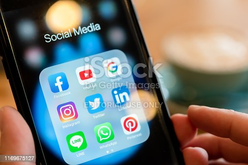 istock BANGKOK, THAILAND- 25 June 2019 : Hands of man use Iphone 7 plus with social media application of facebook, youtube, google search, instagram, twitter, linked in, line whatsapp, and pinterest 1169675127