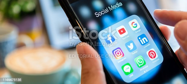 istock BANGKOK, THAILAND- 26 June 2019 : Hands of man use Iphone 7 plus with social media application of facebook, youtube, google search, instagram, twitter, linked in, line whatsapp, and pinterest on black background 1169675135