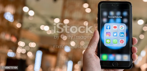 istock BANGKOK, THAILAND- 26 June 2019 : Hands of man use Iphone 7 plus with social media application of facebook, youtube, google search, instagram, twitter, linked in, line whatsapp, and pinterest on black background 1169675164