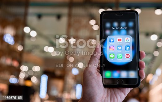 istock BANGKOK, THAILAND- 26 June 2019 : Hands of man use Iphone 7 plus with social media application of facebook, youtube, google search, instagram, twitter, linked in, line whatsapp, and pinterest on black background 1169675165