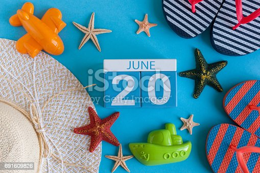 istock June 20th. Image of june 20 calendar on blue background with summer beach, traveler outfit and accessories. Summer day 691609826