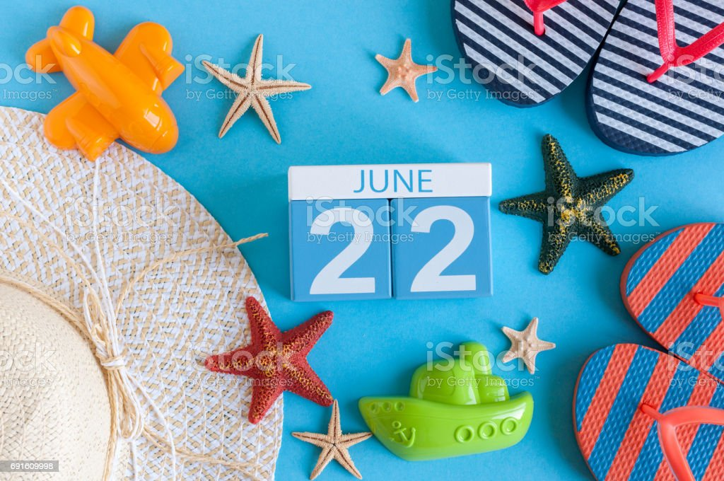 June 22nd. Image of june 22 calendar on blue background with summer beach, traveler outfit and accessories. Summer day stock photo
