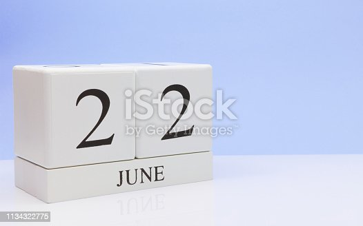 istock June 22st. Day 22 of month, daily calendar on white table with reflection, with light blue background. Summer time, empty space for text 1134322775