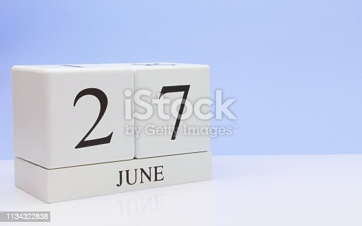 istock June 27st. Day 27 of month, daily calendar on white table with reflection, with light blue background. Summer time, empty space for text 1134322838
