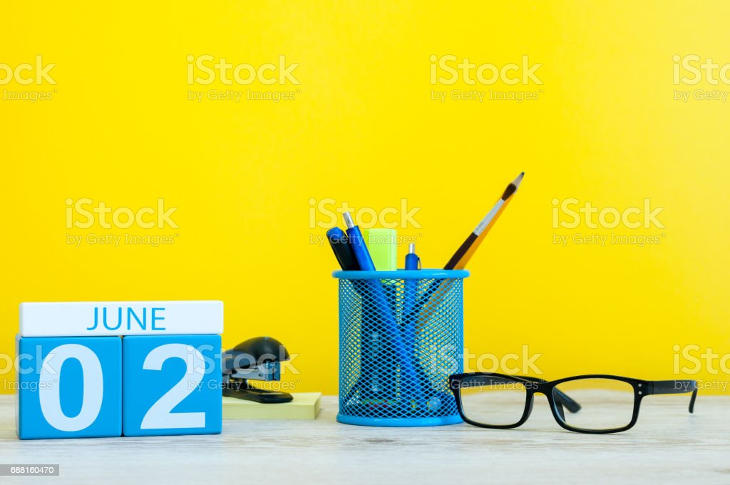 June 2nd. Day 2 of month, calendar on yellow background with office suplies. Summer day, empty space for text stock photo