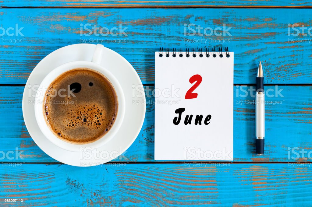 June 2nd. Day of the month 2 , everyday calendar near morning coffee cup at blue wooden background. Summer concept, Top view stock photo