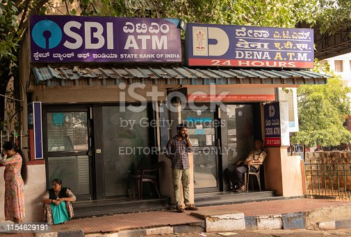 945598452istockphoto BANGALORE INDIA June 3, 2019 :People sitting infront of the SBI ATM and DENA bank ATM's at bangalore railway station. 1154629191
